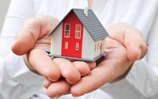 Hausratversicherung Spielzeug Häusschen  in den Händen gehalen